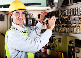 happy male electrician working on industrial machine