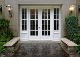 Elegant stone walkway bordered by stone benches leading to a double glass paned front door with two