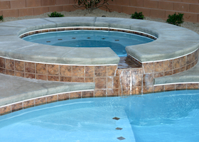 custom jacuzzi and pool with highlighted waterfall grace this desert backyard