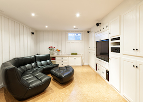 Finished basement of residential home with entertainment center couch and television.
