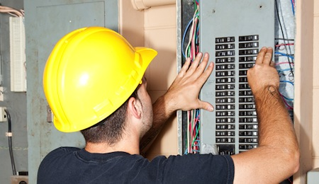Electrician repairing circuit breakers in industrial electric panel.
