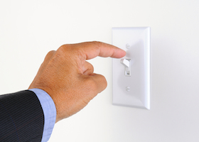 Man's hand with finger on light switch, about to turn off the lights. Closeup of hand and switch only. Horizontal format.